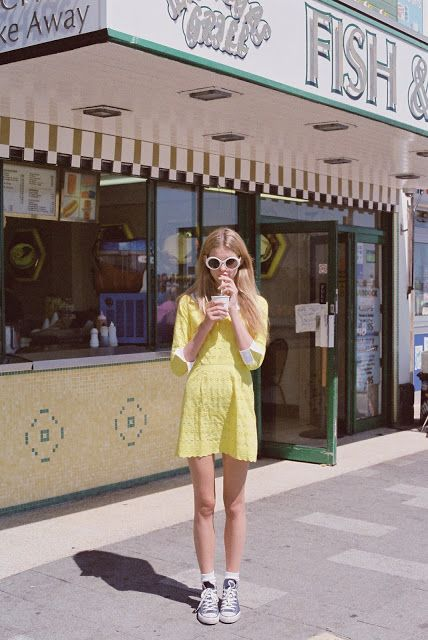 Yellow, white cuffed sleeve dress with a pair of sneakers and round sunglasses for a spring and summer day.