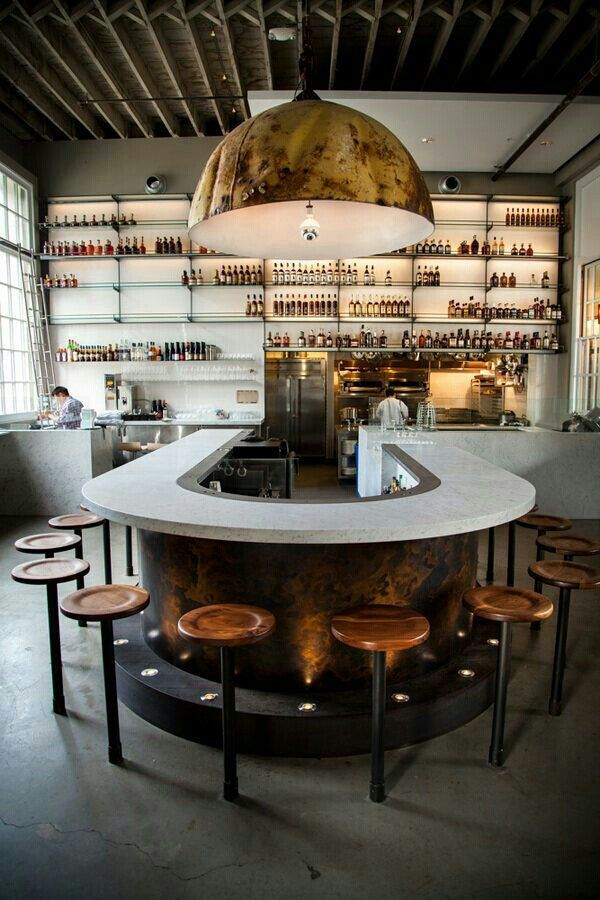 Loving how open this seating arrangement is! A semi-circle configuration makes for excellent conversation. A round-top bar table can achieve this feel in smaller square footage. Extra style points for a brassy light fixture!