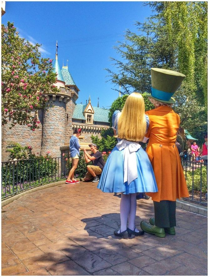 Alice and the Mad Hatter witness a proposal at Sleeping Beauty Castle at Disneyland