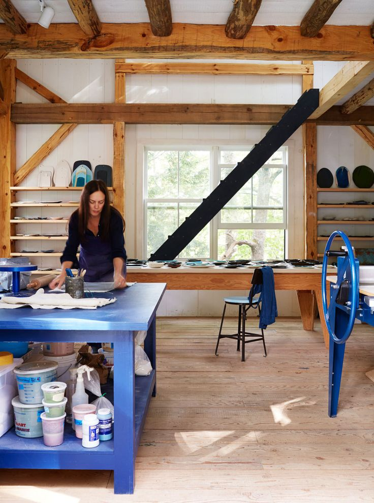 Michael at work in her barn studio, with her cobalt-blue North Star slab roller to her left and pieces from her collection lining the shelves and tablebehind her.