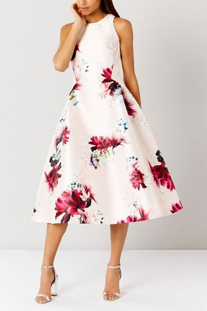 The Minerva Floral Dress Shorter Length has a beautiful flattering style with its round neckline and fit and flare shape which creates a flattering silhouette. The floral print adds a gorgeous twist. This dress measures 102cm from centre back neck to hem. Model wears: UK size 10.