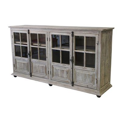 4 Door credenza made of solid mango wood with clear window pane door panels and turn pin black iron locks. The interior back panel are finished in an ivory wash, for contrast.