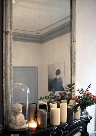 Love the chippy white, ghosted mirror over the glossy black fireplace + a bust on the mantle!