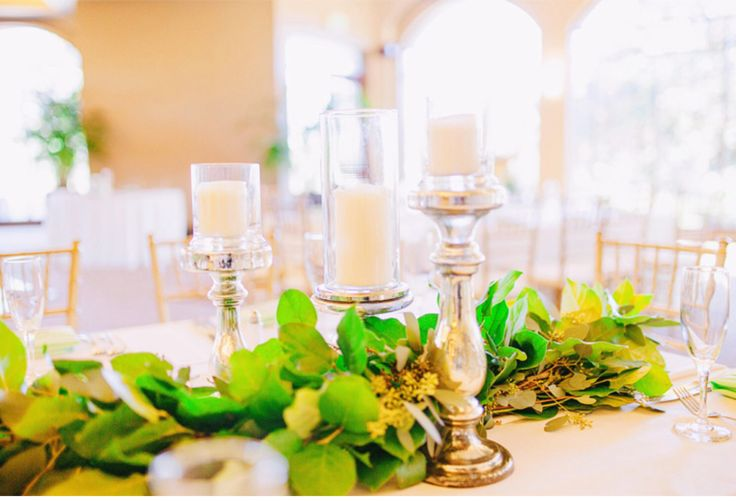 tables were dressed with garland and mercury glass pedestals topped with glass hurricanes and pillar candles