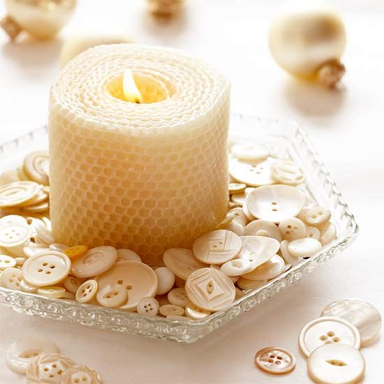 Country Candle Display  Pretty buttons in creamy white surround a beeswax candle to make a cozy display on a holiday table. Use a clear antique dish for continued country charm.