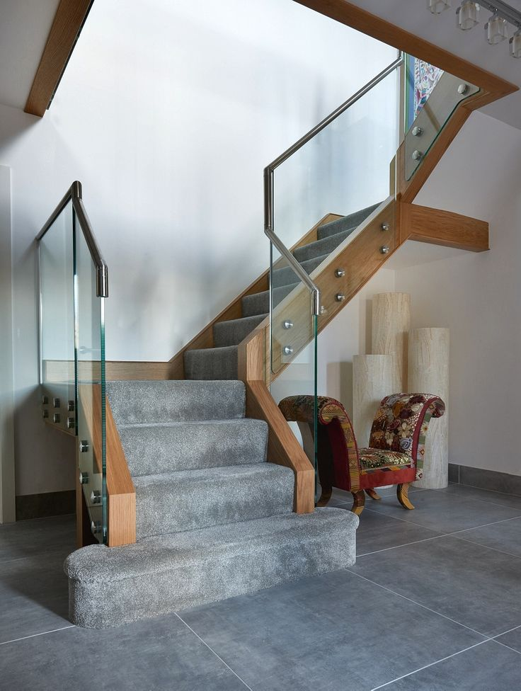 Infinity Integral glass and wood renovation with metal railings and grey carpet. New staircase design for a beautiful home. Decorated with African inspired chaise chair and chunky tall candles. Unique feature step with grey carpet. Photographed by Matt Cant and styled by Nicola Wilkes from My Settled Home.