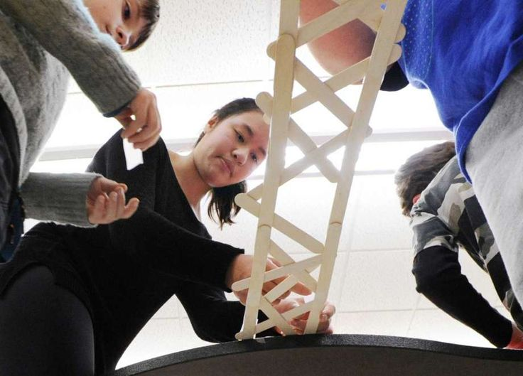 Greenwich High School junior Margaret Cirino, 17, center, helps STEM Explorers after-school club members Christian Zawislack, left, and Michael Orrico, both 9, construct a model bridge using craft sticks at Cos Cob School in Greenwich on Tuesday. Cirino said when she attneds college, she wants to study engineering. Photo: Bob Luckey Jr. / Hearst Connecticut Media / Greenwich Time