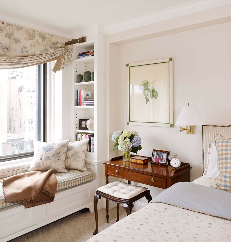 Padded window seat, matching roman blind and curtain.  Lovely small antique desk as bedside table with padded stool, sconces, artwork and flowers.