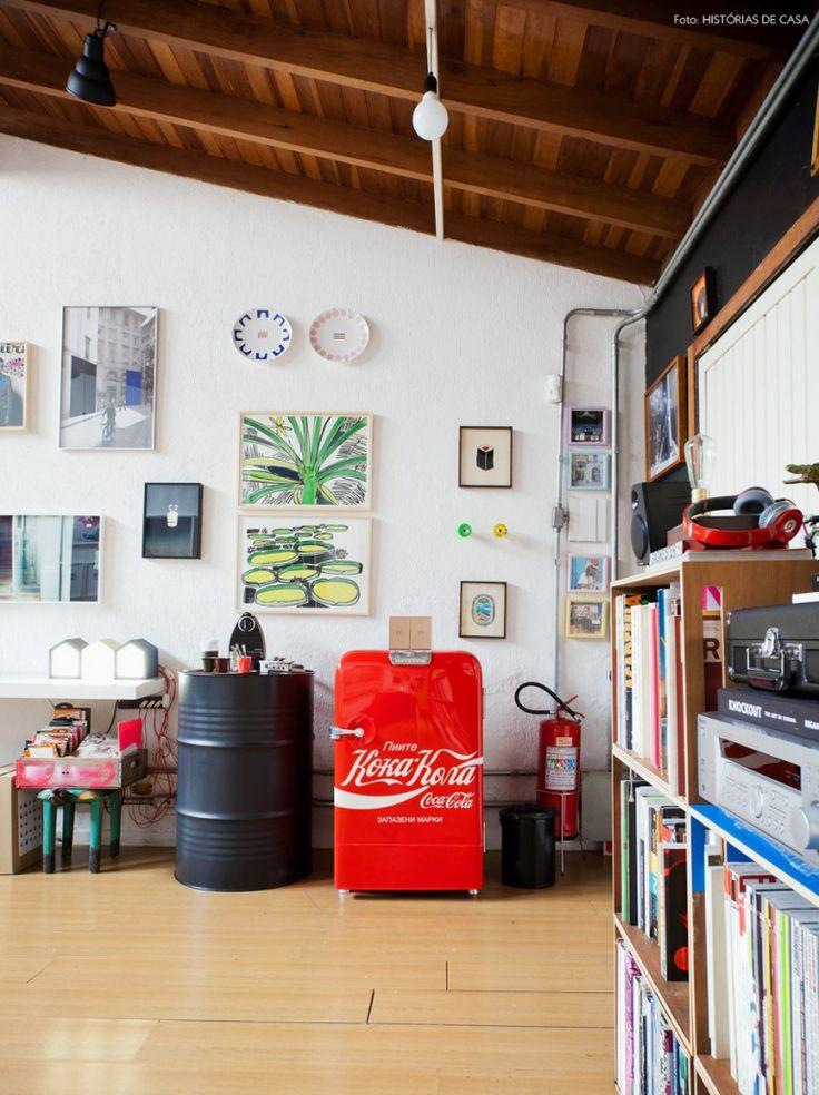 Parede cheia de quadros, tonel preto que serve como mesinha do café e geladeira vermelha da Coca Cola. Vem conferir o escritório super criativo da BG27 (www.bg27.com.br)