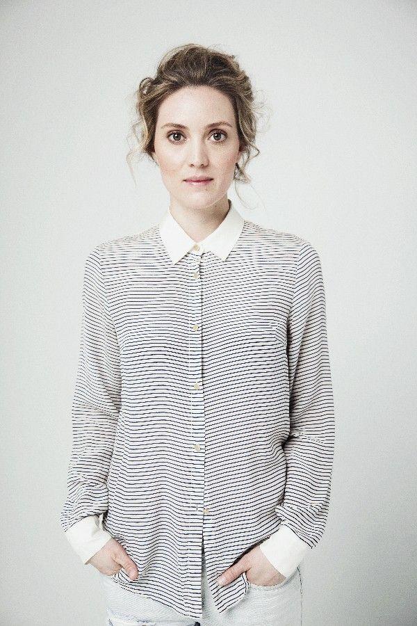 La actriz Evelyne Brochu lleva una camisa a rayas blancas and negros.  La camisa tiene puños blancos, botones, y un cuello blanco