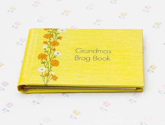 """Another brag book for grandma! This one is a sweet yellow patterned photo book with flower decor and gold foil lettering on the cover that reads """"Grandma's Brag Book"""". Though the pattern looks textured, the surface of the album is smooth.  It is in nice condition overall, but has a"""