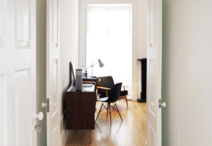 L'ingresso con porte originali dipinte di bianco a una delle ampie camere da letto del bed & breakfast portoghese Rosa Et Al realizzato da Emanuel de Sousa a Porto. Cabinet anni Trenta, sedia DSW Charles Eames per Vitra
