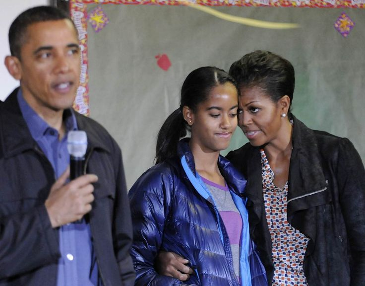 First Lady Michelle Obama stands with her daughter Malia as President Obama delivers remarks during a day of service to honor Martin Luther King, Jr, at the Browne Education Campus school in Washington, January 16, 2012