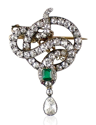 Antique diamond snake brooch designed as a coiled serpent of openwork design, the head set with a single rectangular-cut emerald and ruby eyes suspending a single pear-shaped diamond drop. Victorian or Victorian style.