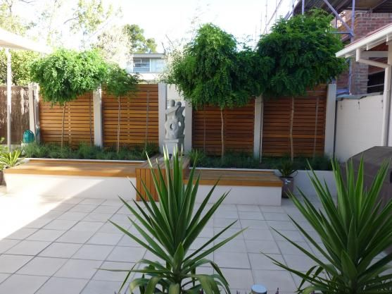 Paving ideas - tiles with wooden benches and backdrop