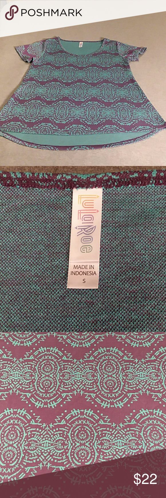 LuLaRoe Classic Tee Style Top Small Geometric Worn once, like new, LuLaRoe women's classic tee top, size small, colors of purple and aqua blue, in an geometric Aztec pattern.   Please see pictures for the measurements.  There is one very small pull, very hard to see in the picture with the pen point.  Longer in back, shorter in front.  Pretty colors and soft, clean too.  I'm petite, only reason why I'm selling this. LuLaRoe Tops Tees - Short Sleeve
