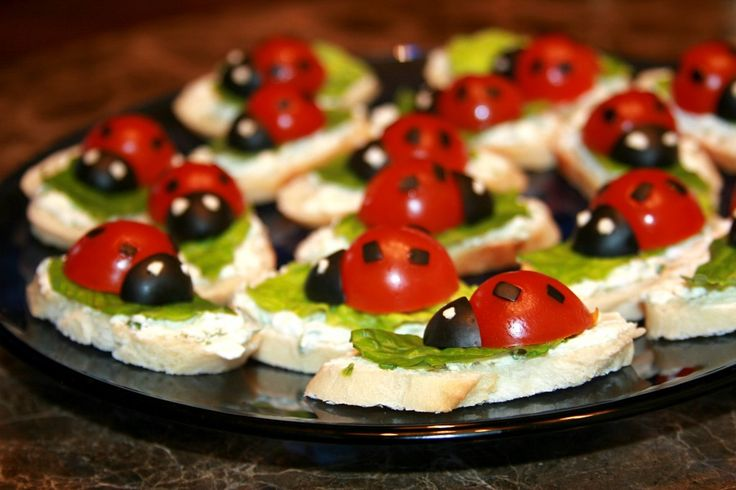 ladybug appetizers                                              15 thin slices of a baguette  1/4 cup sour cream  1/4 cup finely crumbled feta cheese  1 green onion  a couple romaine lettuce leaves  8 cherry tomatoes  8 large pitted black olives