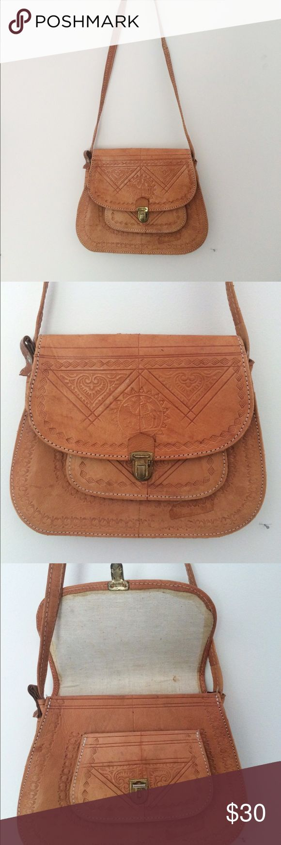 Vintage 1960's/1970's tooled leather saddle bag Circa 1970's tan leather saddle bag with Aztec style tool detail. Comes with shoulder strap and fastens with a metal briefcase clasp. The back has some water damage as depicted and some wear on the strap. Bags Shoulder Bags