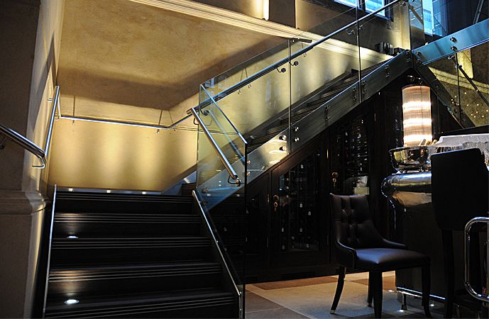 Feature entrance Staircase for fashionable restaurant in London. Mild steel painted carriage with Toughened glass balustrade with stainless…