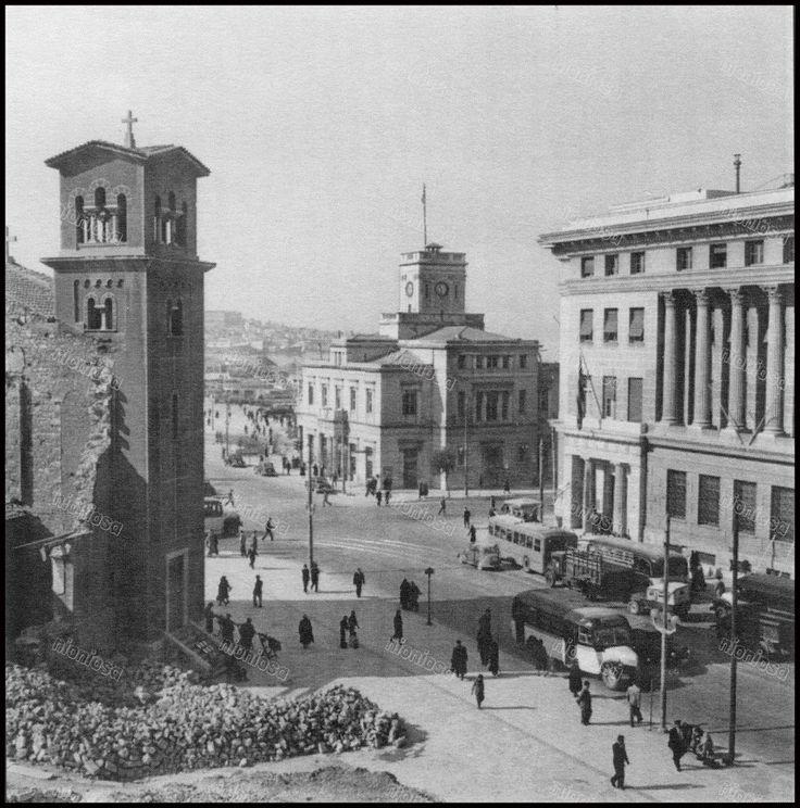 Δεξιά το Μέγαρο ΝΑΤ, στη μέση το Δημαρχείο της Πόλεως, αριστερά η Αγία Τριάδα κατεστραμμένη από τον βομβαρδισμό του Πειραιά στις 11-1-1944. Ο Ναός είχε αποκτήσει τα δύο καμπαναριά επί πρώτης δημαρχίας Σωτήρη Στρατήγη (1934 – 1938).