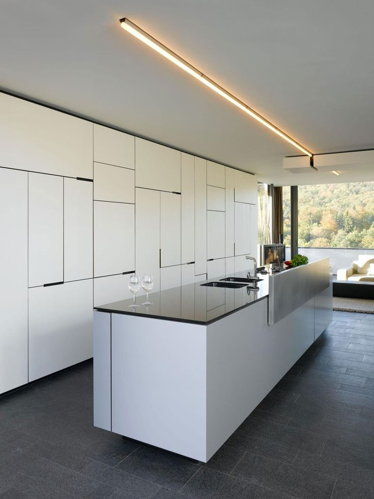 "This modern residence was created by Alexander Brenner Architekten in 2006 and can be found in Stuttgart, Germany. It features a rotating fireplace that divides the living room and the dining area.                House B-Wald by Alexander Brenner Architekten: ""Two anthracite-coloured building volumes glittering in the sunlight can be seen from the road. The gate in between them opens to a private world. From up here, one looks down to the residence, a building composed of light-coloured…"