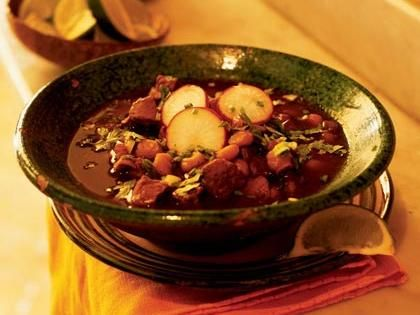 Pork Posole | Try this thick and hearty red posole recipe, the Mexican soup that's perfect for a one-dish meal. There are three main versions of this hominy stew, each representing a color of the Mexican flag. Red posole, like this version, is made from dried chiles; our stew features ancho chiles. The green version is made from fresh chiles, and white posole has no chiles.