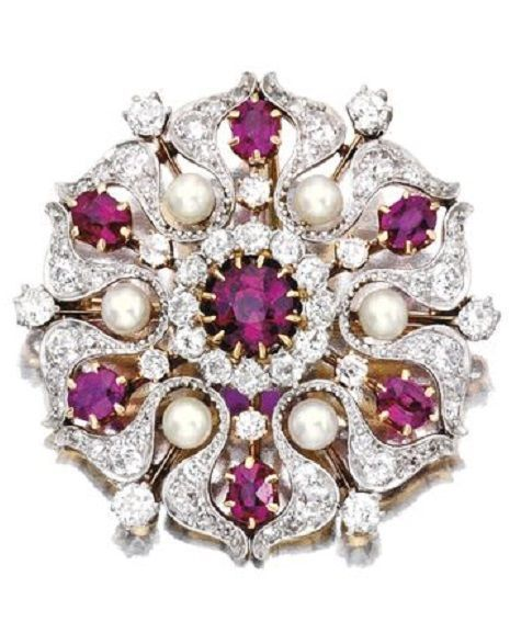 Platinum, Gold, Ruby, Diamond and Pearl Brooch, Pickslay & Co. The stylised flowerhead centring a round ruby framed by six oval-shaped rubies and six pearls, accented by old European and rose-cut diamonds, signed Pickslay & Co.; circa 1900; fitted with pendant hook. Z #DiamondBrooches #diamantebroochesfordresses