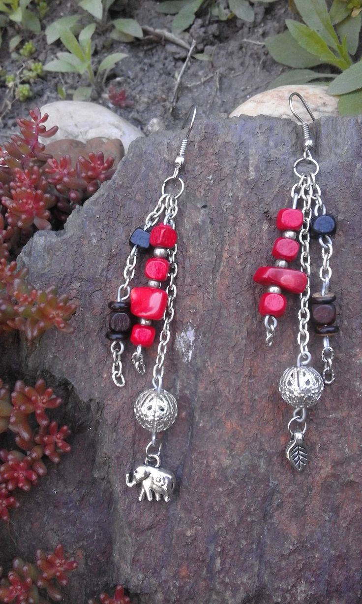 Long chain earrings with tiny silver medals, and brown and red beads.