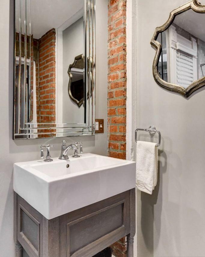 Egy kevés tégla felület mosdó mellett, fürdőszobában, tükrökkel