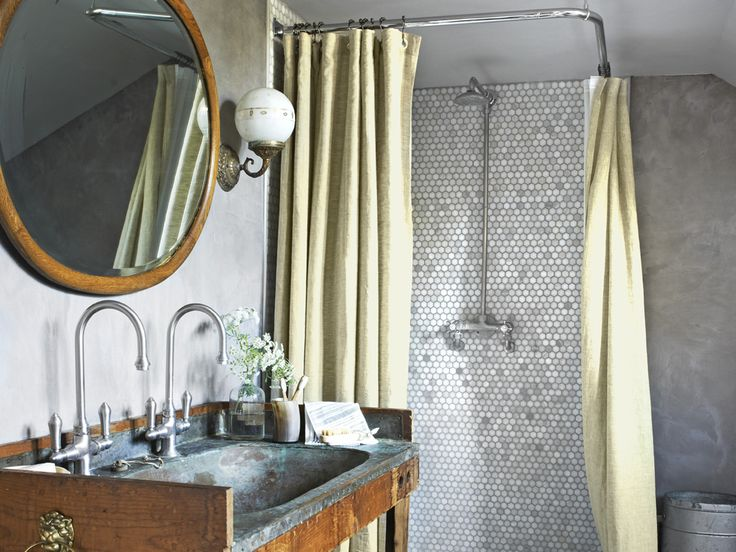 An old copper sink basin (with two faucets), antique sconces and a vintage tub bring back a sense of history to this bathroom space.   - CountryLiving.com