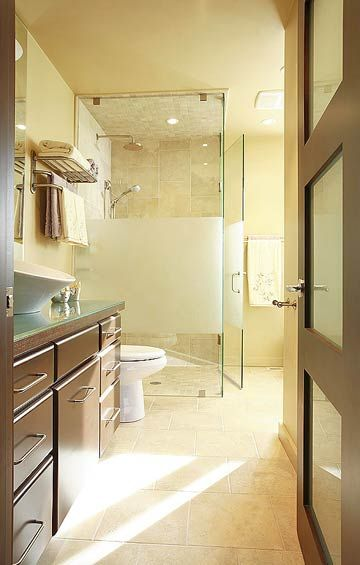 The shower enclosure is a combination of clear and frosted glass to allow for privacy as well as elegance. Dark-stained cabinetry contrasts beautifully with the light tones of the flooring and walls.