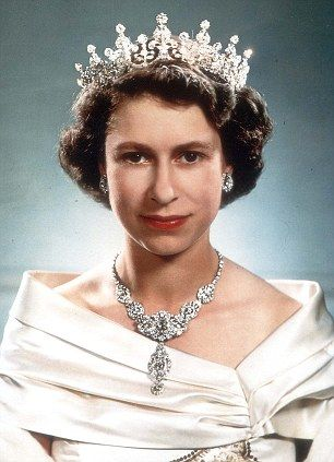 The Queen, pictured wearing an evening dress of white satin embroidered in leaf design with gold thread, diamonds, and pearls