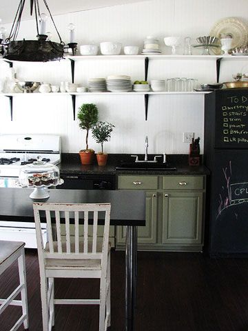 To eke out more space in the small kitchen, add an open island from IKEA. High stools in a worn paint finish add to the lived-in look. A vintage chandelier found at a flea market replaced the fluorescent light and added much-needed drama. Lighting stores can rewire most anything.