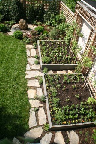 nicely designed raised bed garden incorporated into small yard + slate pavers.