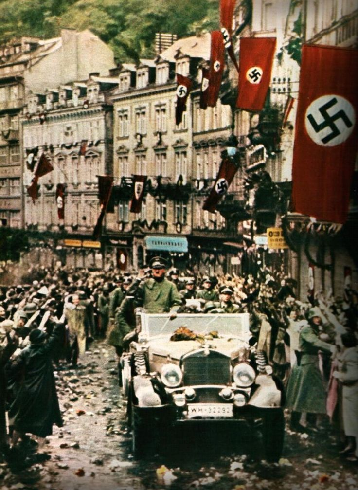 Greeted by tens of thousands of enthusiastic Austrians, Hitler accompanied by his motorcade travel en route to the capitol building in Vienna, Austria to proclaim the unification of the German Reich with the lands in which he was born. This monumental event came to be known as the Anschluss. March 12th, 1938.
