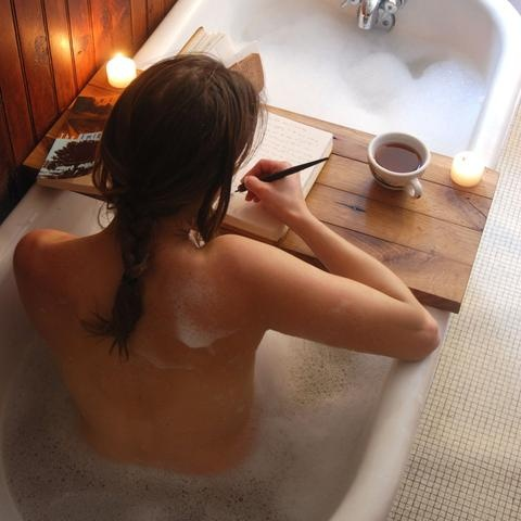 A deep soaking tub and desk for a book to read, tea,