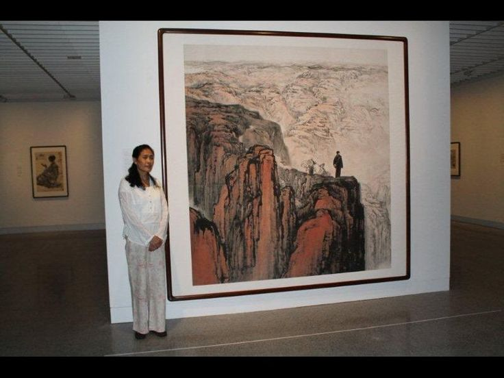 Shi Dan stands next to the painting that nearly cost her father's life (Radio New Zealand)