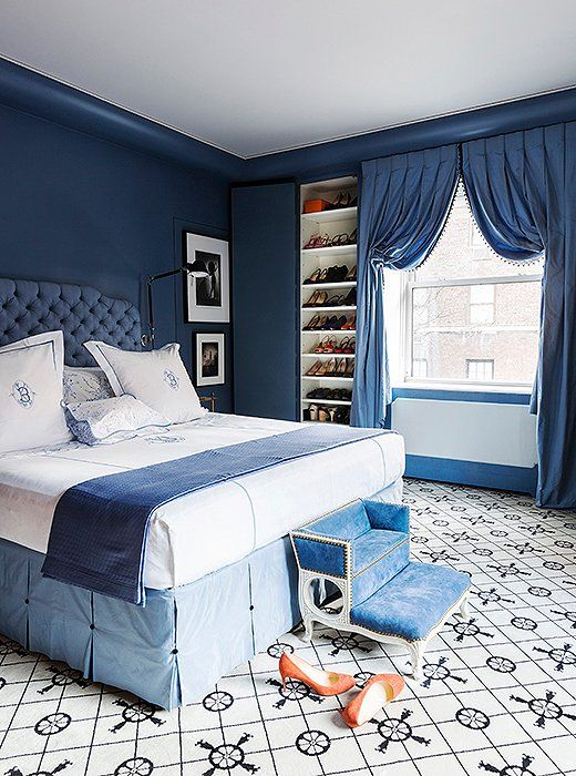"Farrow & Ball's Pitch Blue informed the design of the master bedroom. ""Once we decided on the blue for the walls—a color I feel is so French—I thought, Let's be super French about it,"" says Kate. ""So I put in the Madeleine Castaing carpet and went with a really deep French-style tufting on the headboard."" A step stool at the foot of the bed completes the look. Purchased at John Rosselli, it was a 12th-birthday gift from Kate to her dog, Lucy."