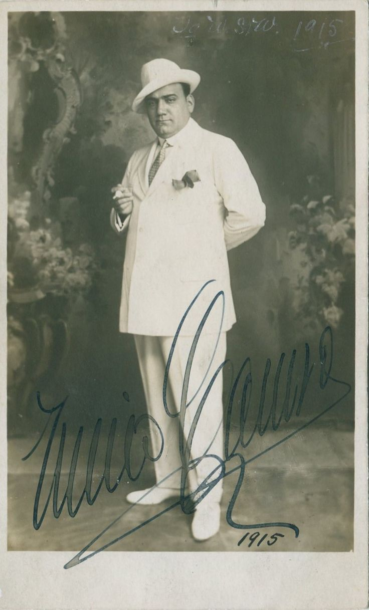 CARUSO ENRICO: (1873-1921) Italian Tenor. Vintage signed postcard photograph, an appealing image of Caruso standing in a full length pose. Signed ('Enrico Caruso') in bold fountain pen ink with his name alone to a light area at the base of the image. Neatly dated 1915 in ink in another hand beneath his signature.