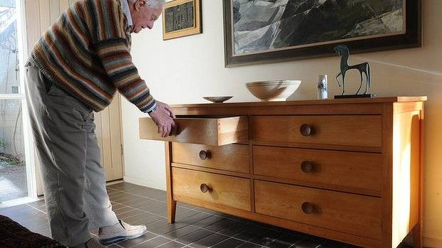 Furniture designer, Derek Wrigley at his Mawson home. He is writing a book about his fellow designer, Fred Ward. Derek opens a drawer of a chest, designed by Fred.
