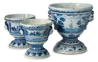 An assembled continental Delft garniture of three blue and white landscape-decorated krater-form flower pots, 18th century