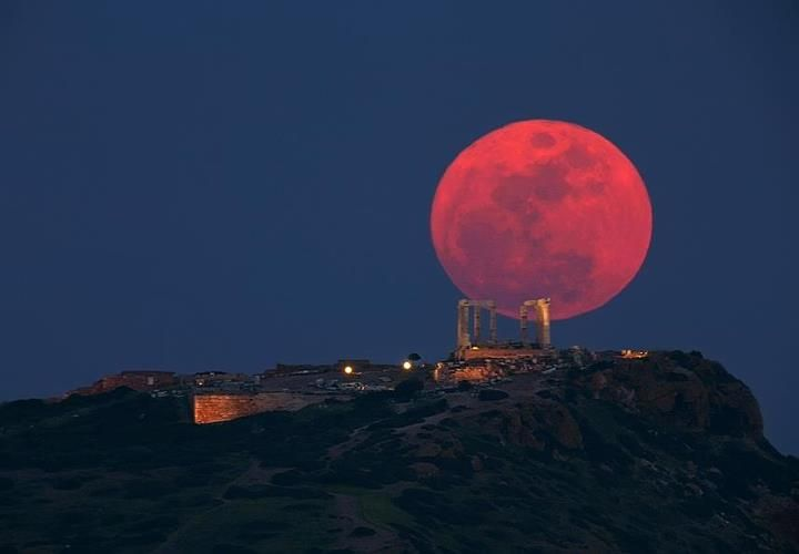 Blood red lunar eclipse over the Temple Diana in Greece