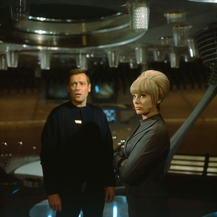 "Dietmar Schönherr (as Major Cliff Allister McLane) and Eva Pflug (Lt. Tamara Jagellovsk - GSD-officer, ""Galaktischer Sicherheitsdienst"", German for ""Galactic Security Service"", the military intelligence service) in Raumpatrouille – Die phantastischen Abenteuer des Raumschiffes Orion (1966)."