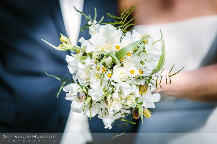 Bruidsboeket in witte tinten met witte rozen, witte lathyrus, witte pioenrozen en margrieten.