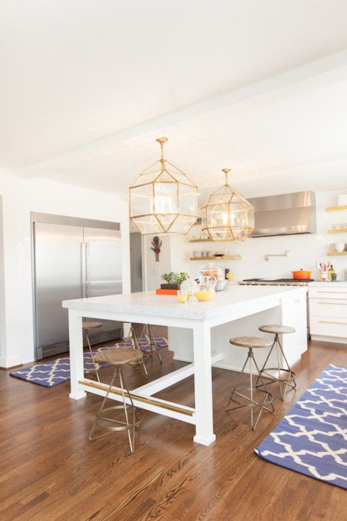 U shaped kitchen features Suzanne Kasler Morris Lanterns in Gilded Iron illuminating island with legs lined with vintage wood top barstools facing gold floating shelves flanking stainless steel hood over high-end gas range