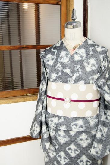 生成り色とネイビーブラックのバイカラーで織り出された大きな斜めチェックと、アヒルが向かい合うようなキュートなモチーフがモダンな正絹紬の単着物です。