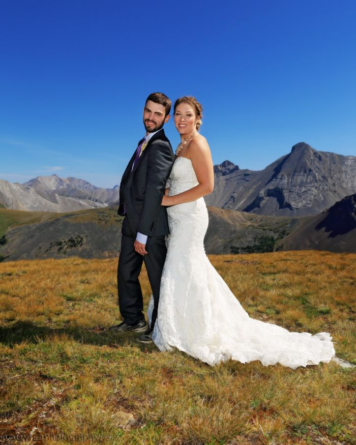 Bride & groom holding each other on grassy slope of mountain side in Canmore Alberta. Summer heli-wedding. Canmore Alberta wedding.