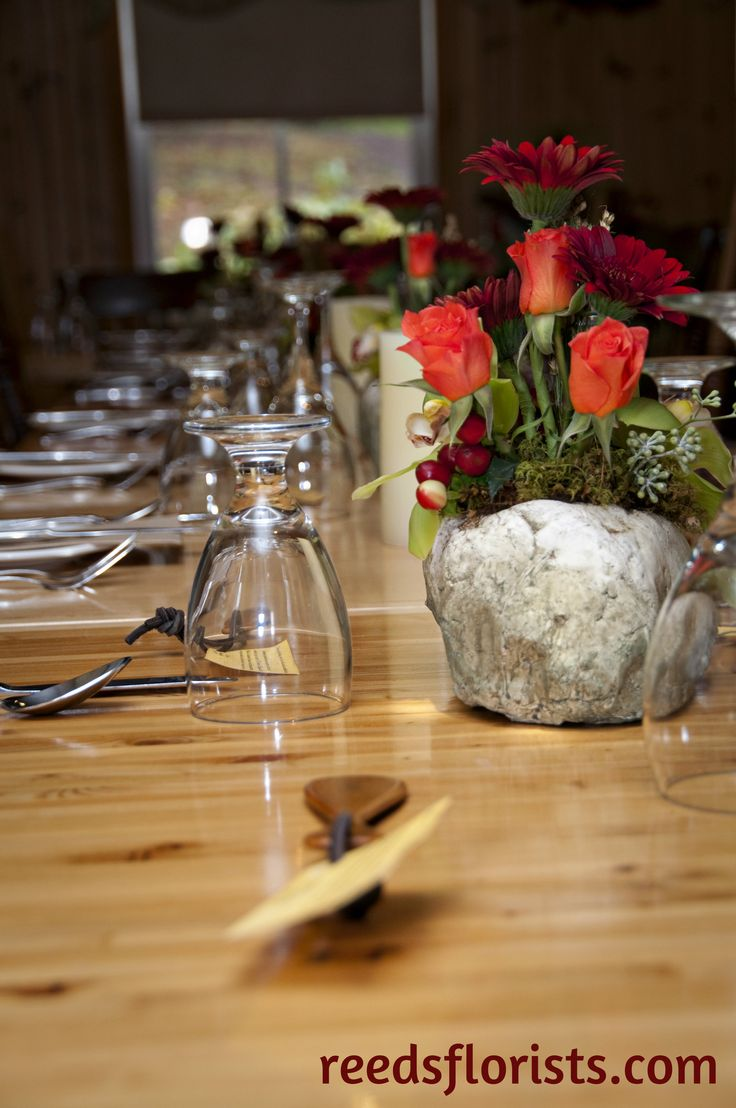 """Gerberas, roses and orchids in a unique """"stone"""" container repeated along the bare wood tables complete the rustic theme."""