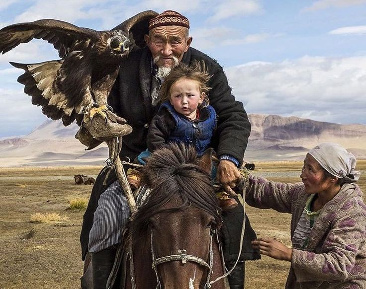 A Kyrgyz man & his grandson hunting with an eagle in the Altai Mountains.