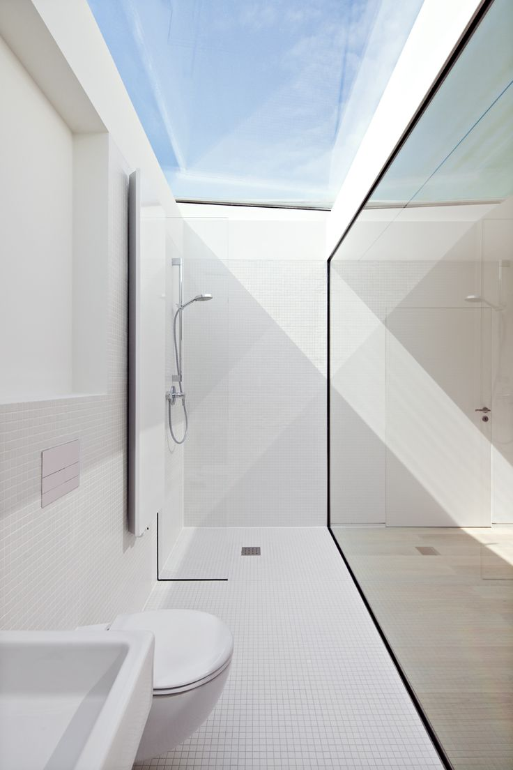 the well crafted cuboid by ian shaw architekten generates ethereal light, a dramatic interplay of light and shadow within a bathroom setting.